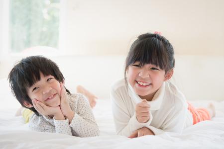 흰색 침대에 누워 귀여운 아시아 어린이 스톡 콘텐츠