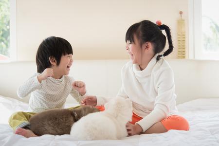 Kleine Aziatische kinderen die puppy op wit bed kussen