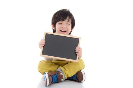 Leuke Aziatische jongen die zwarte bord op een witte achtergrond geïsoleerde