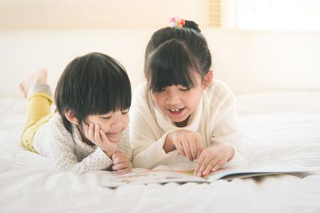 Niños asiáticos lindos libro de lectura en la cama blanca, filtro de la vendimia