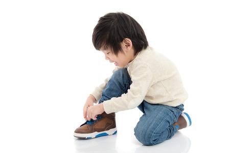 weinig Aziatische jongen koppelverkoop zijn schoenen geïsoleerd in een witte achtergrond