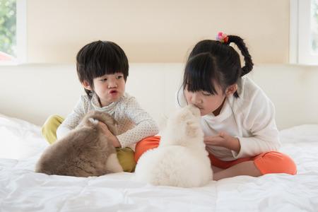 Little asian children kissing puppy on white bed