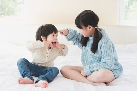argue kid: Asian sister and brother quarreling on white bed