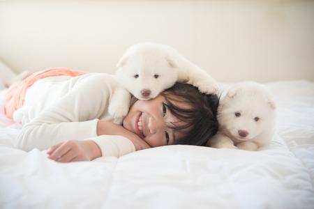 2 つのシベリアン ハスキー子犬のベッドの上で横になっている小さなアジアの女の子