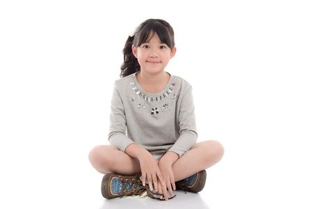 Schöne asiatische Mädchen sitzt auf weißem Hintergrund isoliert Standard-Bild