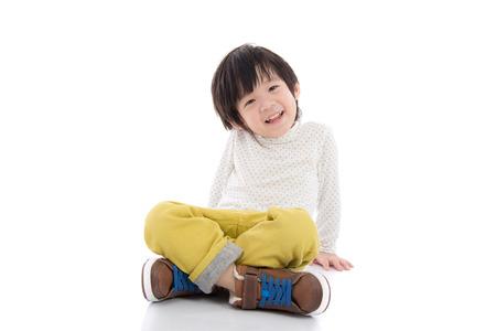 Happy asian boy sitting on white background isolated