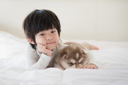 puppy love: Niño asiático lindo y cachorro de husky siberiano acostado en la cama blanca Foto de archivo