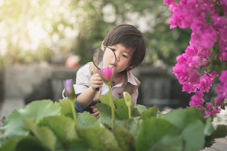 Asian boy with magnifying glass outdoors,vintage filter Stok Fotoğraf