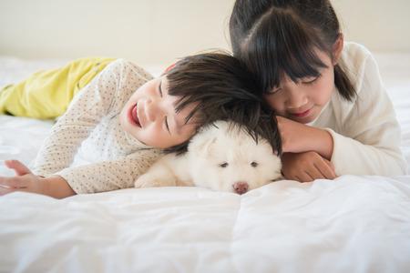 アジア子供白いベッドの上で横になっている白いシベリアン ・ ハスキー