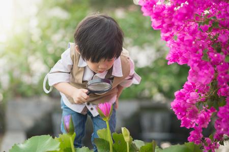 Ragazzo asiatico con la lente d'ingrandimento all'aperto
