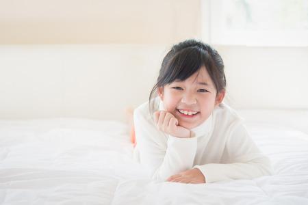 Felice ragazza asiatica sdraiata sul letto