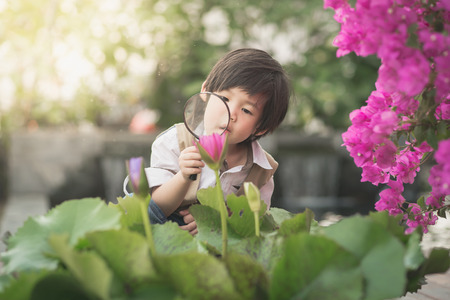Asian boy with magnifying glass outdoors,vintage filter Standard-Bild