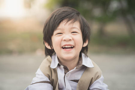 アジアの少年の笑い、ビンテージ フィルターの肖像画を間近します。
