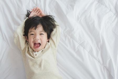 reir: Niño asiático lindo acostado en la cama blanca