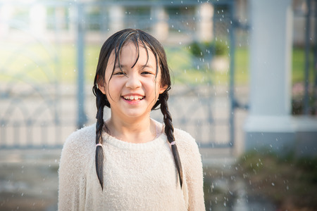 rain wet: Beautiful asian girl is happy with the rain