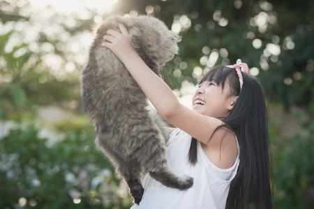 美しいアジアの女の子公園で太陽の光と美しいペルシャ猫を保持