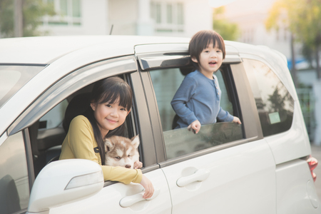animal family: Happy asian children and siberian husky puppy sitting in the car Stock Photo