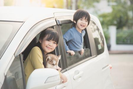 Niños asiáticos felices y cachorro de husky siberiano que se sienta en el coche Foto de archivo