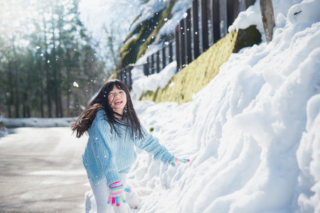 Happy asian girl smiling outdoors in snow on cold winter day Stok Fotoğraf