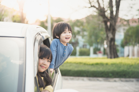 Happy asian children sitting in the car