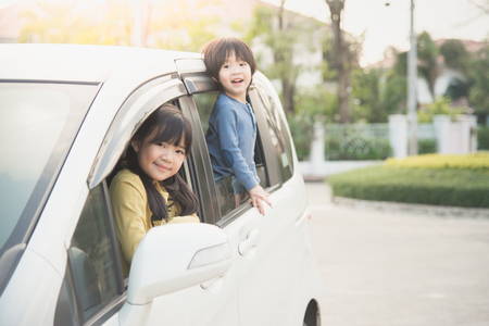 Happy asian children sitting in the car Stockfoto