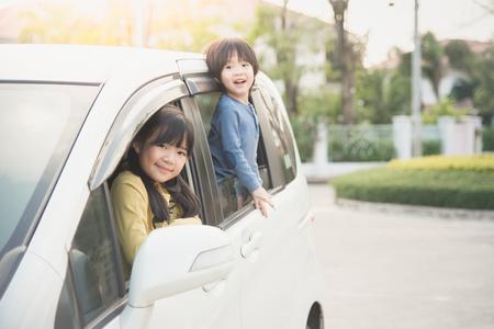 familias jovenes: Niños asiáticos felices que se sientan en el coche