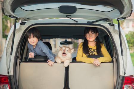 Gelukkige Aziatische kinderen en siberische husky puppy zitten in de auto