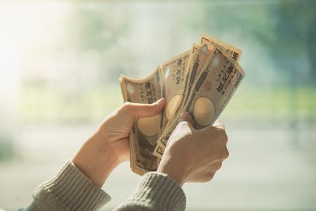 De hand van de vrouw het tellen geld, Japanse muntnota, Japanse Yen