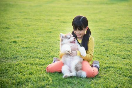 puppy love: muchacha asi�tica hermosa que juega con el perrito del perro esquimal siberiano en el parque