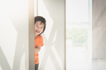 Cute asian child hiding behide the wall Banco de Imagens - 54880513