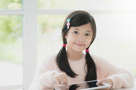 Mooi Aziatisch meisje met behulp van tablet op witte lijst