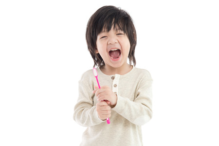 Cute asian child brushing teeth on white background isolated