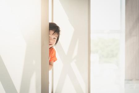 Leuk Aziatisch kind ondergedoken behide de muur