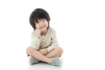 sit up: Happy asian boy sitting on white background isolated