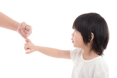 dedo meÑique: Madre e hijo haciendo una promesa de meñique en el fondo blanco aislado Foto de archivo