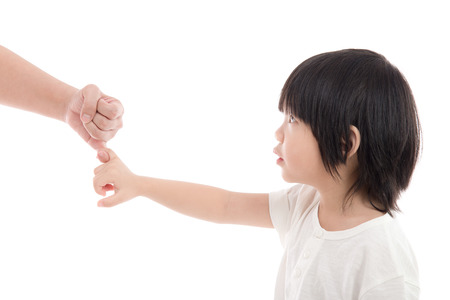 Mother and son making a pinkie promise on white background isolated