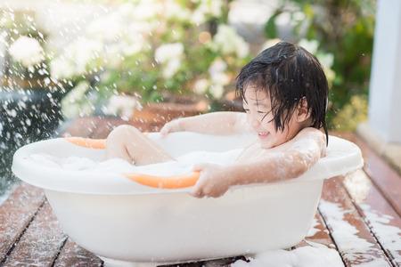 庭のお風呂かわいいアジアの子 写真素材