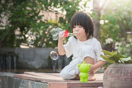 funny boy: Cute asian child is blowing a soap bubbles Stock Photo