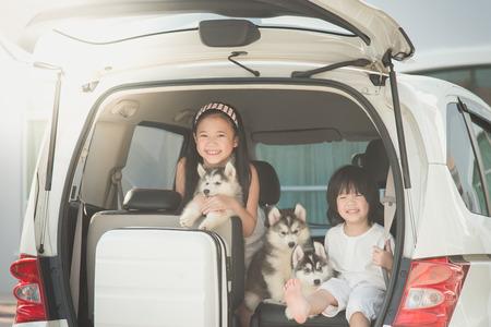Heureux les enfants asiatiques et siberian husky pupp ??? assis dans la voiture
