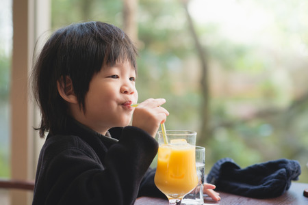 Cute asian child drinking fresh orange juice