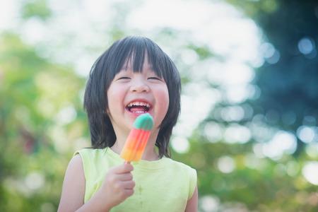 屋外アイス クリームを食べるかわいいアジアの子
