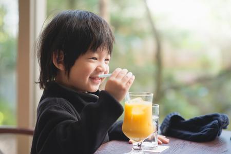 新鮮なオレンジ ジュースを飲むかわいいアジアの子