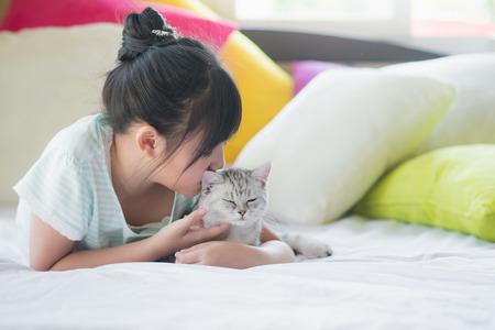 Beautiful asian girl kissing american shorthair cat on the bed Stock fotó