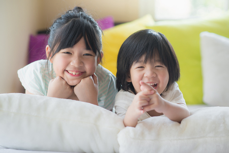 Cute asian children lying on white bed Zdjęcie Seryjne - 57368226