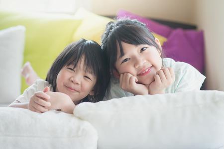 Leuke Aziatische kinderen liggen op wit bed