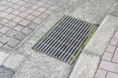 Close up of sewer manhole cover in a city street