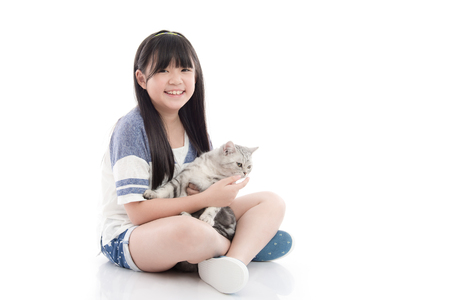 pet cat: Beautiful Asian girl playing with lovely tabby kitten on white background,isolated