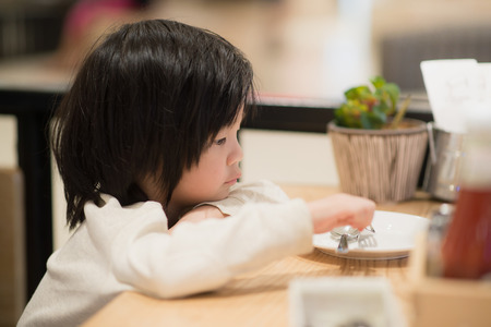 japanes: Cute Asian child holding a spoon and fork with empty white plate  in restaurant Stock Photo