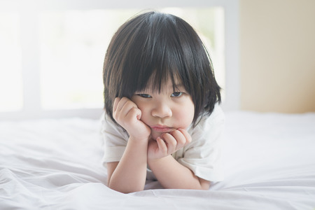 Portrait of unhappy asian baby lying on white bed Stock Photo