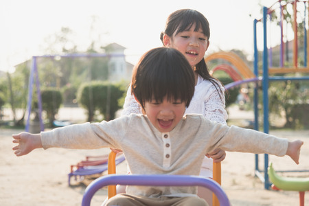 totter: Cute asian children riding seesaw board at the playground under sunlight